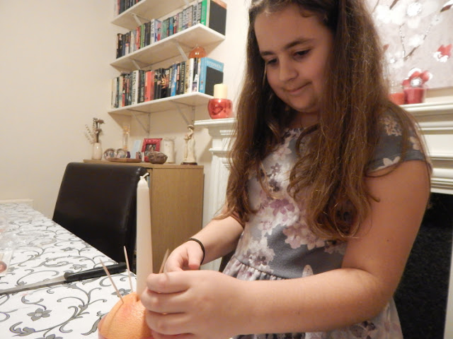 KayCee sticking cocktail sticks into her orange for the sweets to go on