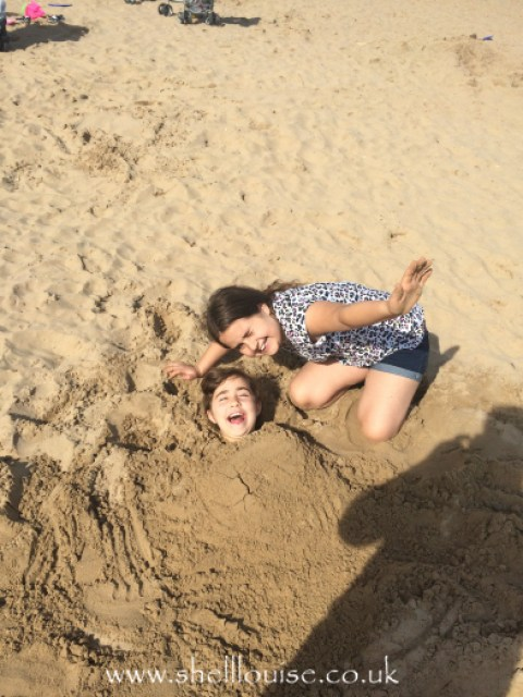 Kaycee burying Ella in the sand