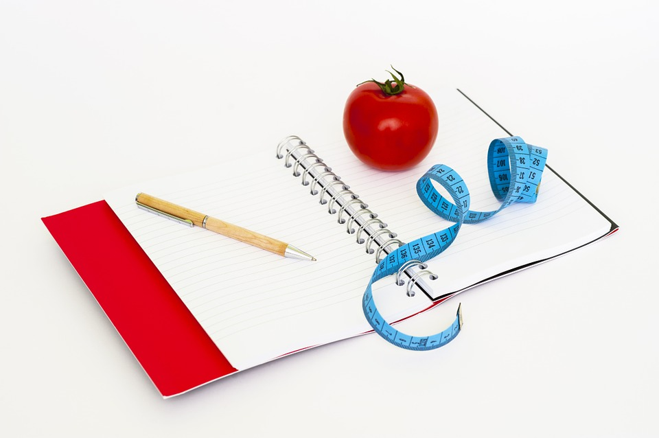 food diary. pen, tomato and tape measure 3.5 pound loss