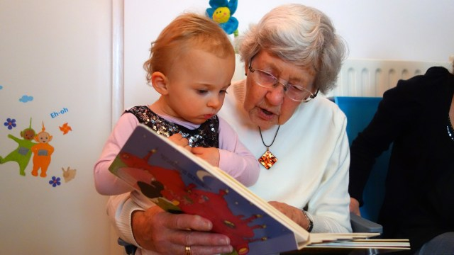 grandmother reading to grand daughter
