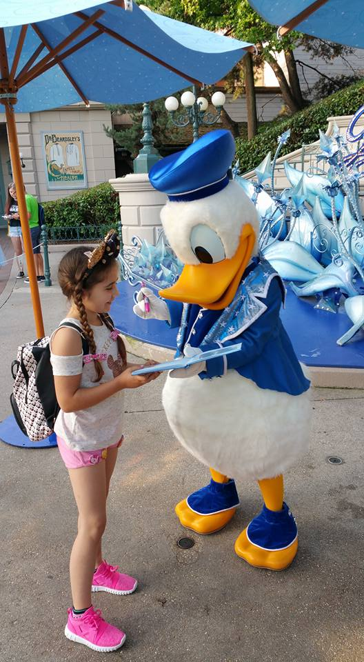 Donald Duck signing Ella's autograph book - Disneyland Paris Photos