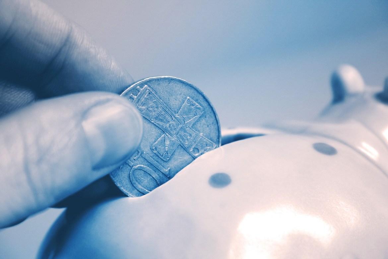 a coin being put into a piggy bank