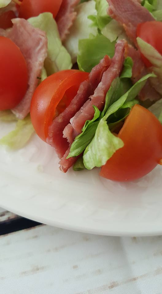 BLT bites - cherry tomato with lettuce and bacon on a cocktail stick