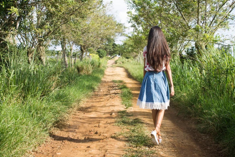 teenage girl walking down a dirt track