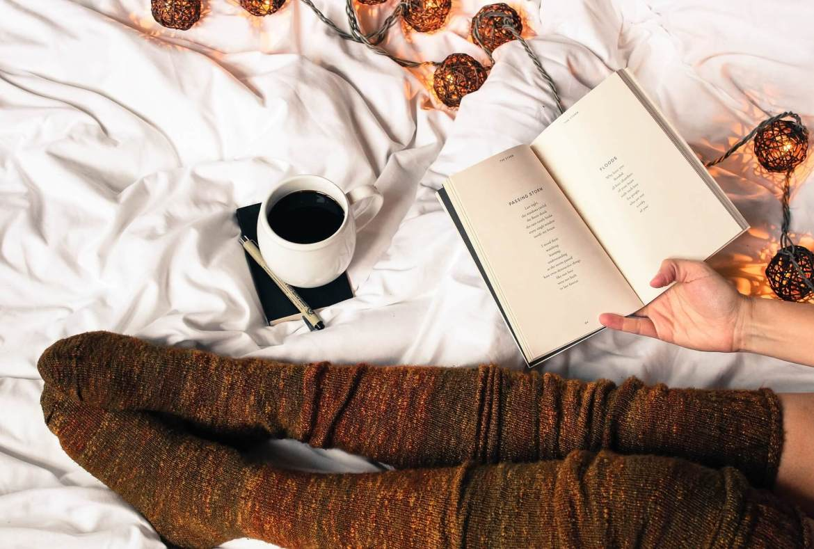 cosy Autumn bedroom - paid of legs on a bed, cup of coffee, open book and string lights