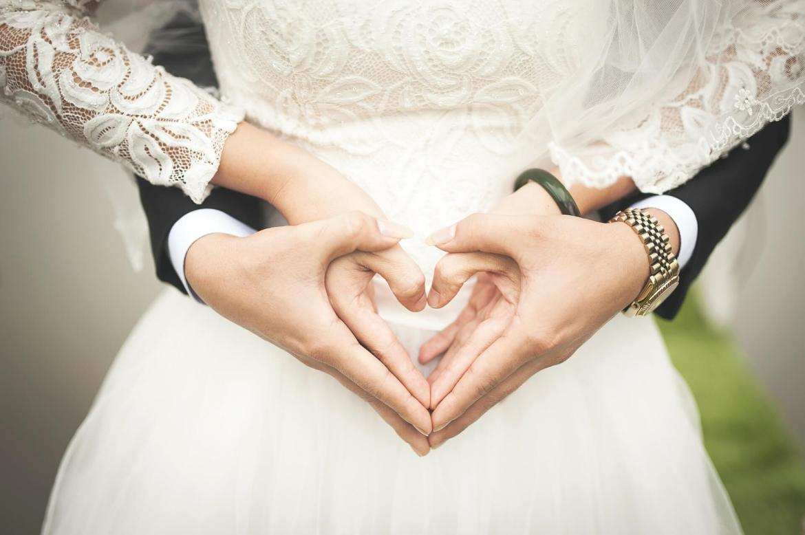 summer wedding - bride and groom's hands making a heart shape together