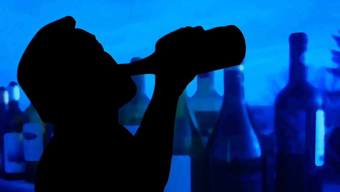 silhouette of a man drinking a bottle of alcohol - addiction