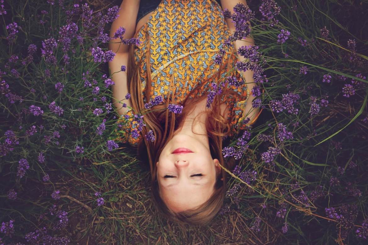 self-love - lady lying down in a field of lavender flowers
