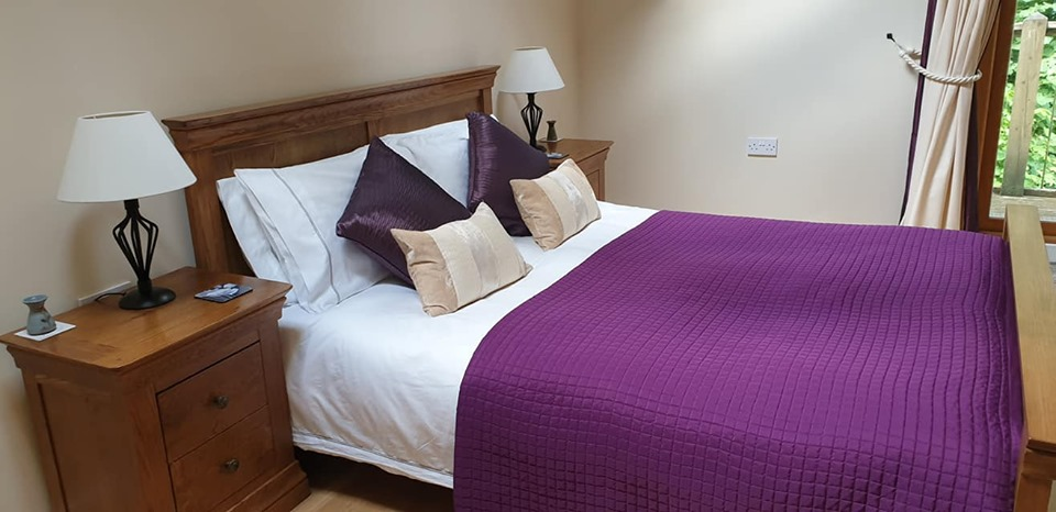 double bed with purpple and white bedding at Felin Fach cottage, Pumsaint, Wales