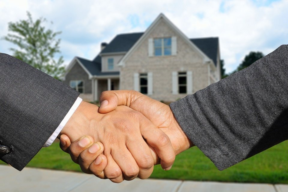 Estate agent shaking hands with a house buyer