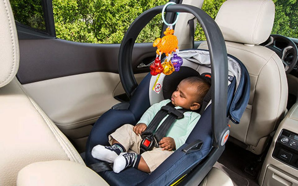 baby in a car seat in the back of the cr