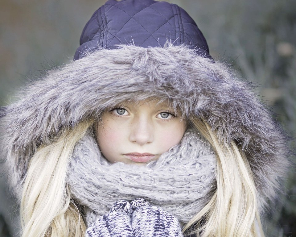 child dressed in a winter coat and wearing a scarf