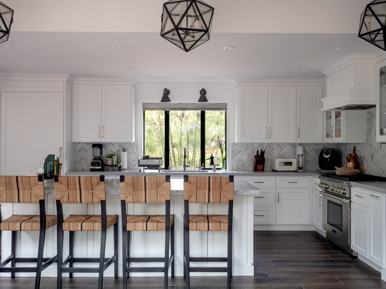 white kitchen with black light and serena and lily chairs
