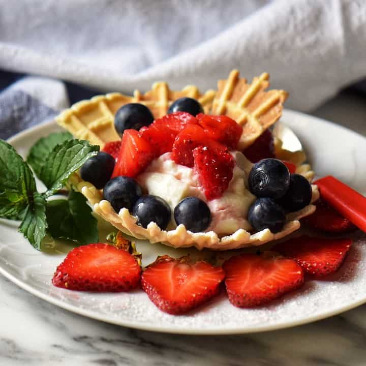 Pizzelle shaped in a bowl and filled with whipped ricotta and macerated strawberries.