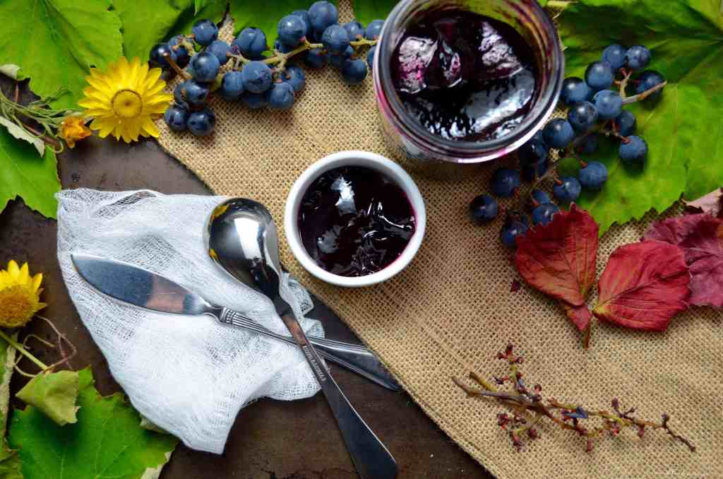 An overhead shot of the grape jelly in a small bowl along side some fresh grapes.