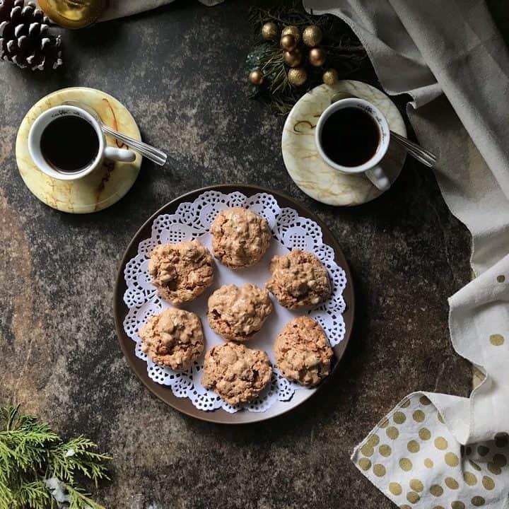 An overhead shot of a platter of brutti ma buoni cookies along side 2 espressos.