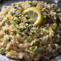 Creamy risotto topped with parsley and a lemon slice.
