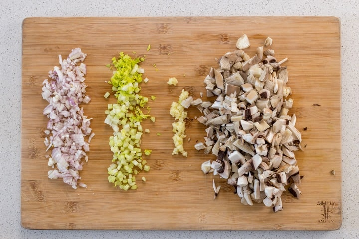 Chopped shallots, celery, garlic and mushrooms on a wooden board.