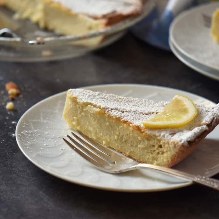 A slice of old fashioned Italian pie made with ricotta, on a white plate, dusted with icing sugar.