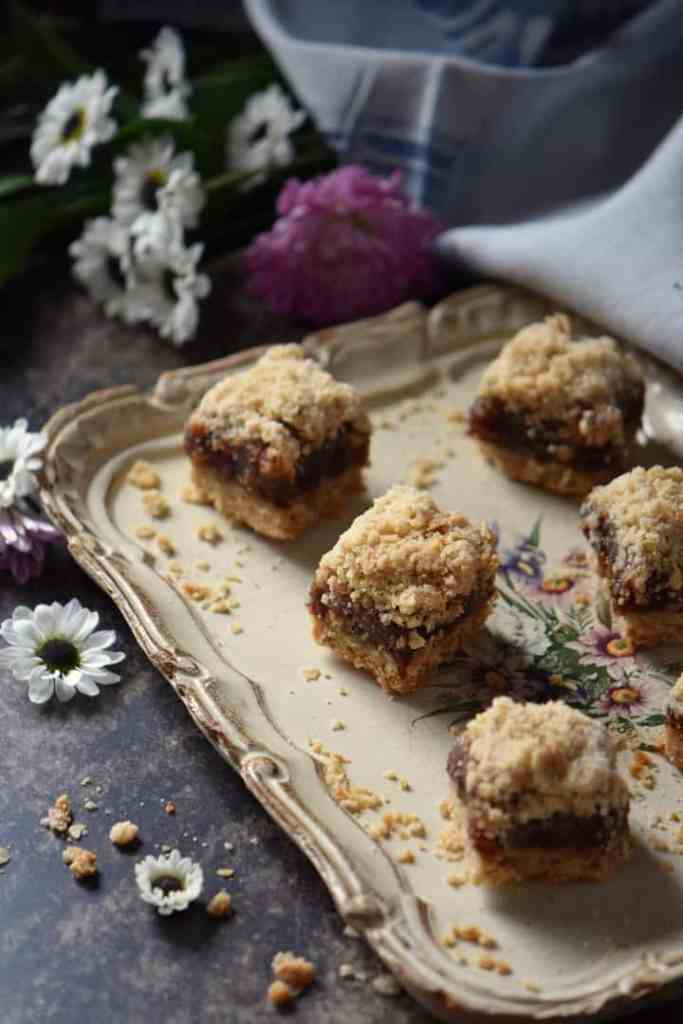 Date squares in a tray, surrounded by white daisies.