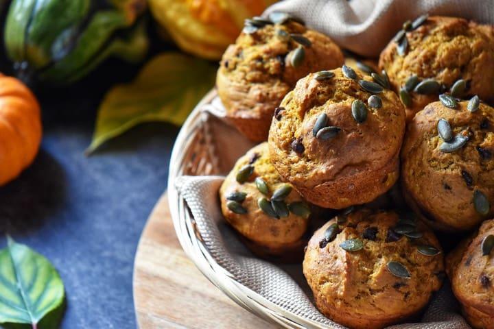 A basket of pumpkin muffins next to squash and mini pumpkins.