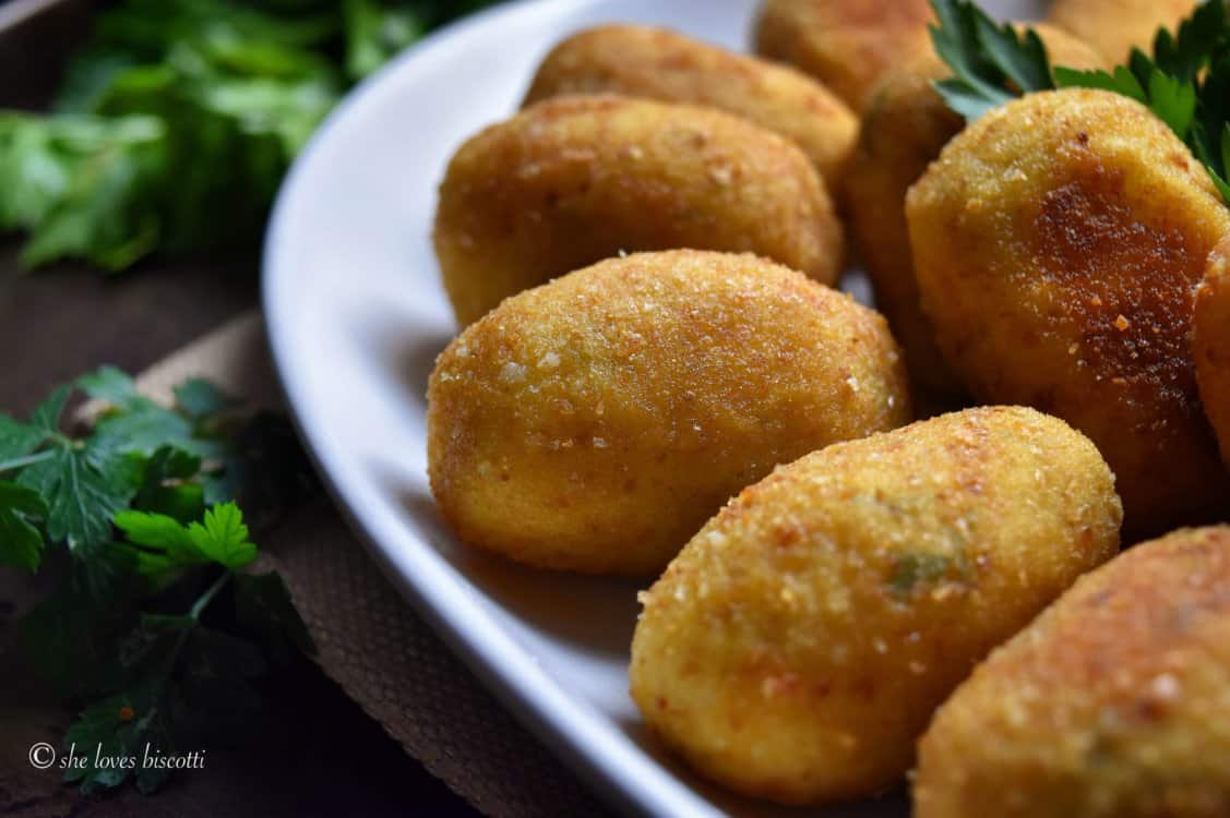 Croquettes are seen on a white serving platter.