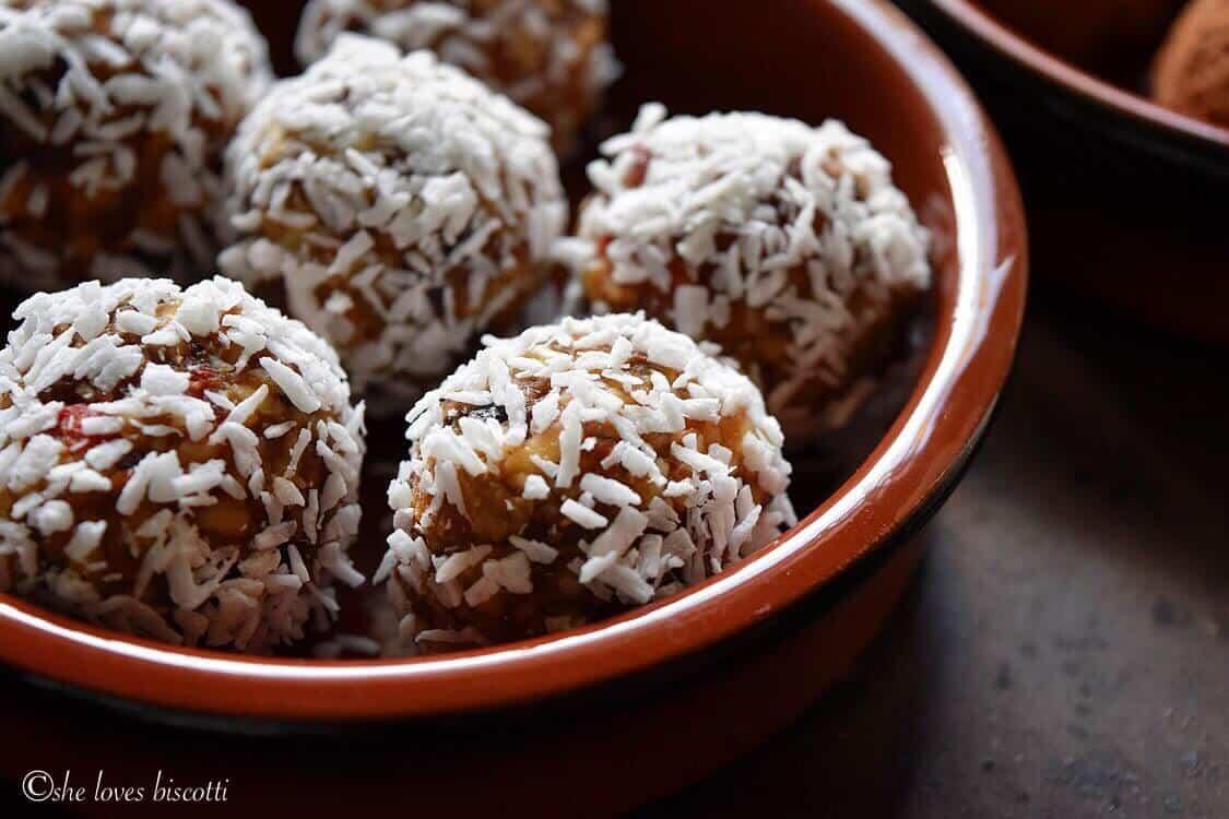 A bowl of unsweetened shredded coconut covered Greek Yogurt Goji Berry Almond Date Energy Bites