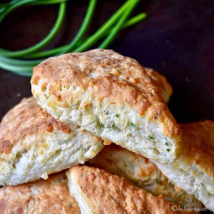 A close up of garlic scapes Cheese Biscuits piled on top of each other.