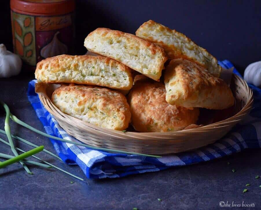 Fluffy garlic scape cheddar biscuits in a wicker basket, set on a blue checkered tea towel.