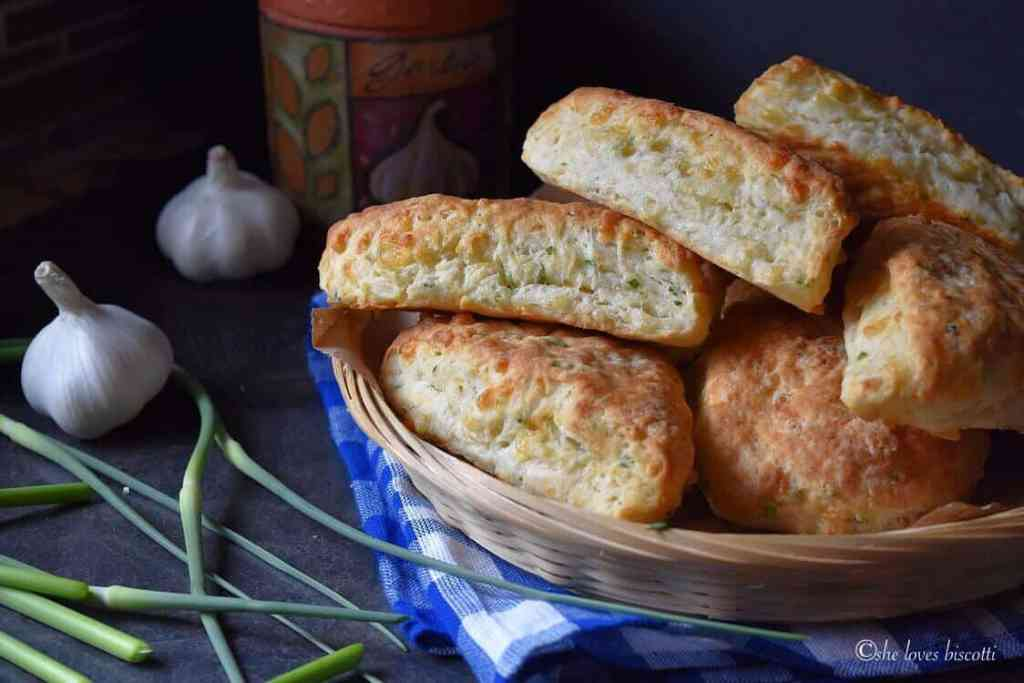 A basket of Cheese Biscuits surrounded by fresh garlic scapes.