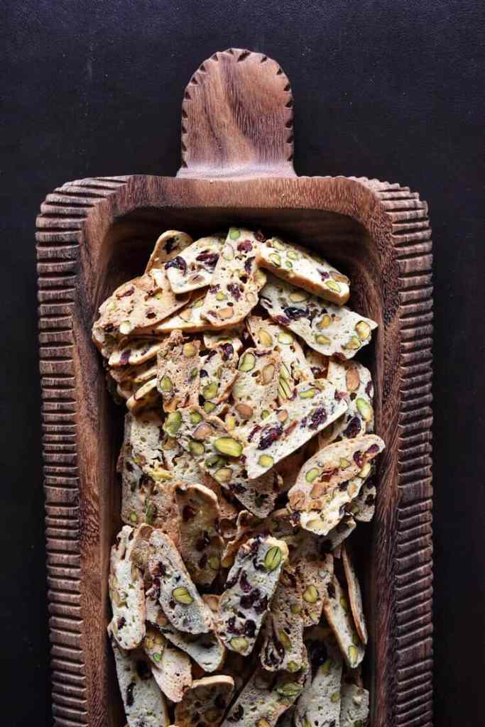 Overhead shot showing thin cranberry pistachio biscotti in a big wooden serving platter.