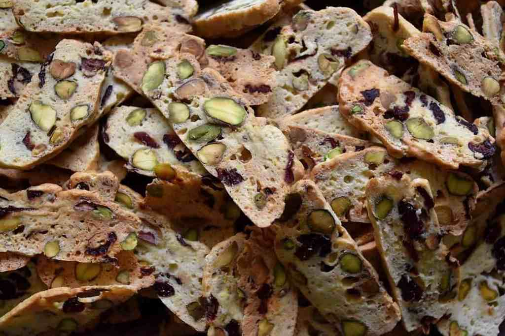 An overhead shot of dozens of colorful thin Cranberry Pistachio Biscotti