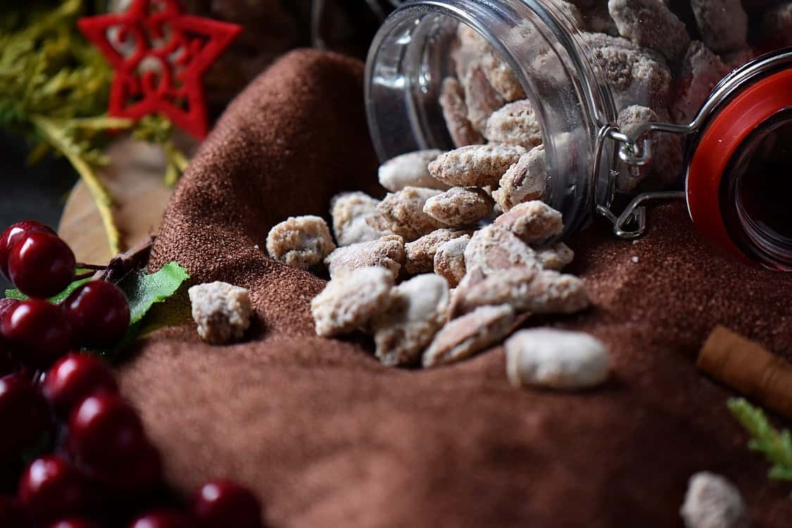 Another picture of the mason jar of Oven Roasted Sugar Almonds spilled on a brown tablecloth.