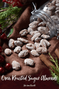 The mason jar of Oven Roasted Sugar Almonds spilled on a brown tablecloth.