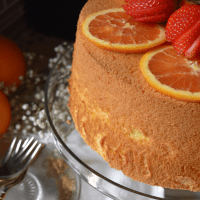 The Orange Chiffon Cake is is a cake platter decorated with sliced oranges.