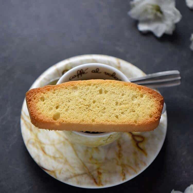 A close up of a single Italian anise biscotti on an espresso cup.