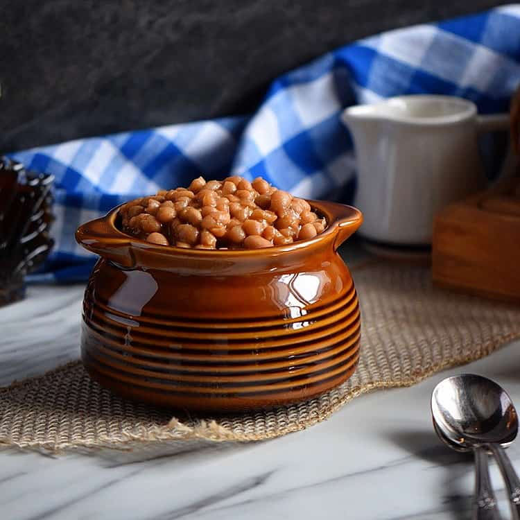 A side view of a brown ceramic dish of baked beans.
