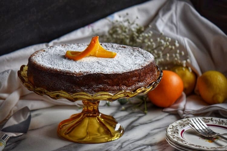 Rice ricotta Easter pie on a cake stand surrounded by oranges and lemons in the background.