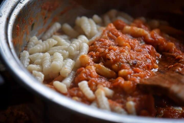 Roasted red pepper sauce and cavatelli being combined.