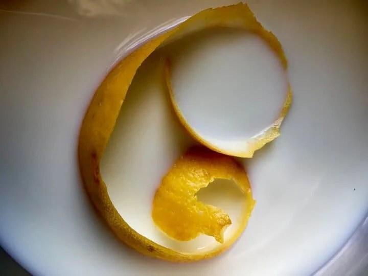 The addition of lemon peel to milk.