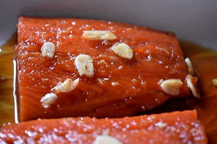 A close up of the garlic slivers on the salmon.