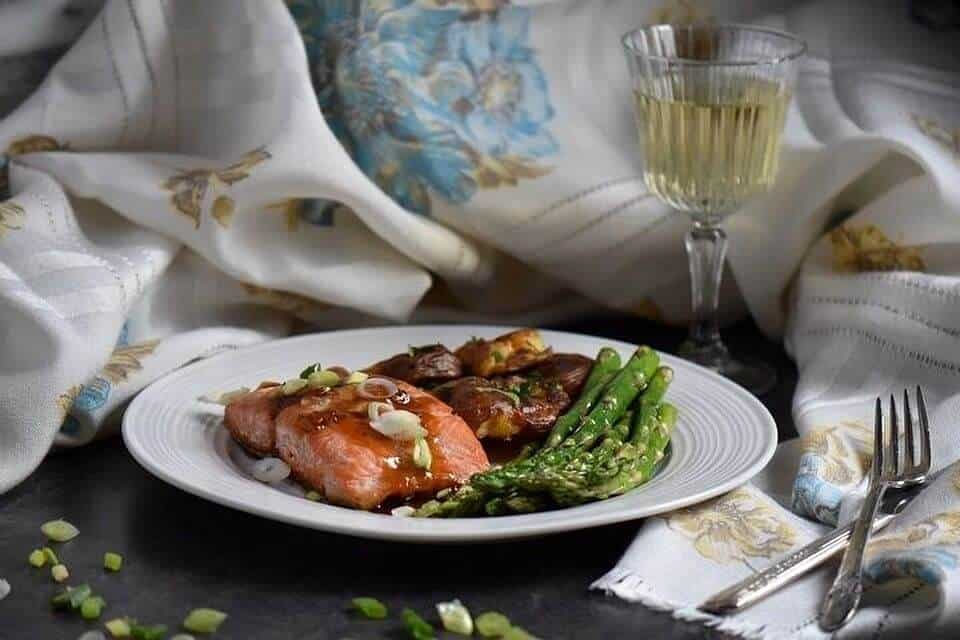 A piece of glazed salmon served on a white plate along with sauteed asparagus and smashed potatoes.