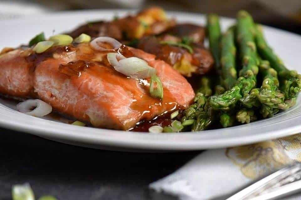 A close up picture of a maple glazed salmon served on a white plate.