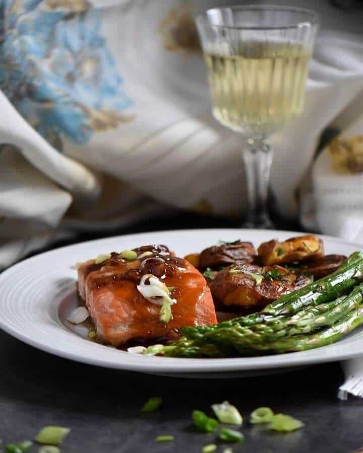A dinner plate complete with glazed salmon, sauteed asparagus and smashed potatoes with a glass of white wine in the background.