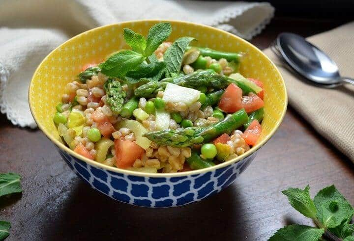 The colorful spring salad in a colorful yellow and blue patterned bowl.