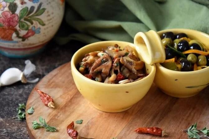 Marinated Mushrooms along side marinated olives, both in yellow bowls.