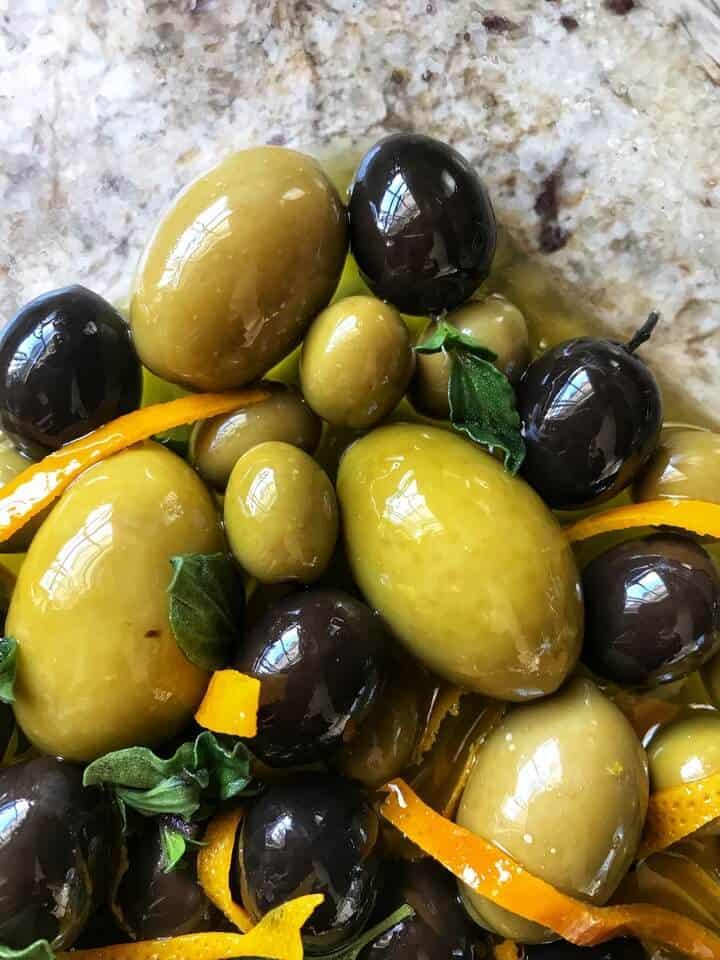 An overhead shot of marinated olives with orange zest and oregano.