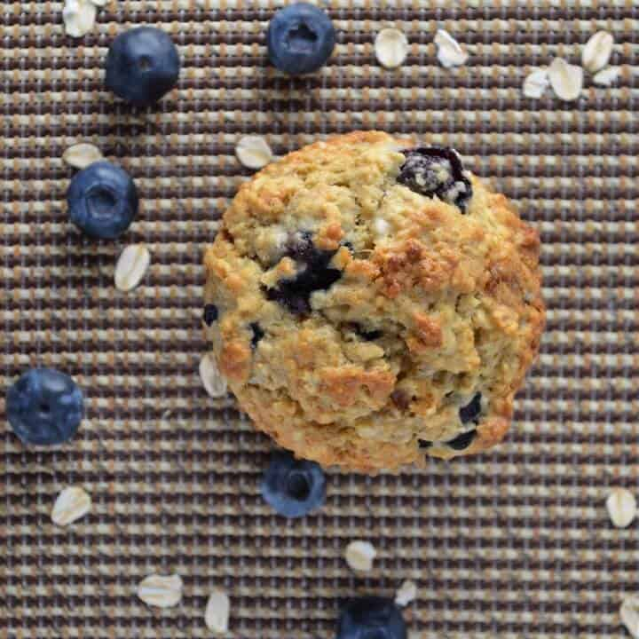 An overhead shot of a blueberry muffin surrounded by blueberries and large flakes of oats.