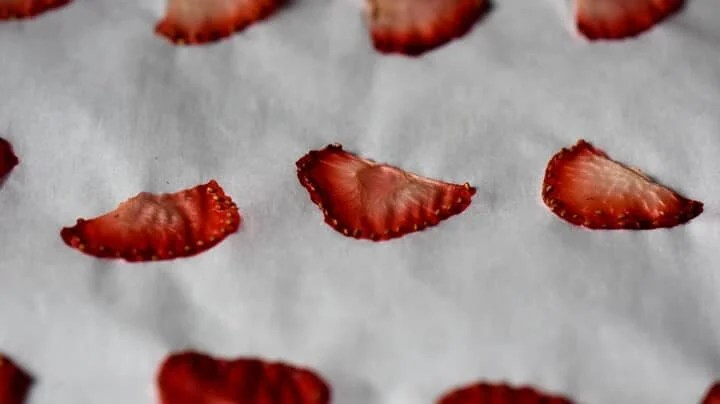 Visibility dehydrated strawberries on a parchment lined baking sheet.
