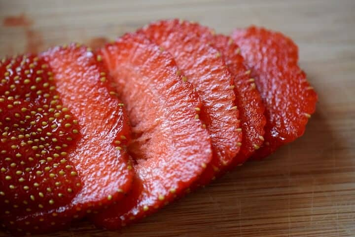 A sliced strawberry on a wooden board.